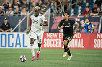 FOXBOROUGH, MA - AUGUST 4: Wilfried Zahibo #23 of New England Revolution with Carlos Vela #10 of Los Angeles FC in pursuit during a game between Los Angeles FC and New England Revolution at Gillette Stadium on August 3, 2019 in Foxborough, Massachusetts.