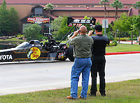 Apr 23, 2015; Pearland, TX, USA; NHRA top fuel driver Shawn Langdon (right) takes a photo of his dragster during a sponsorship announcement with Bass Pro Shops at the Pearland, TX store. Mandatory Credit: Mark J. Rebilas-