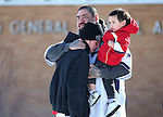 Marty Happy, holding his son Ryder, 2, hugs David Mosier after they recieved word that a group of six people had been found alive after being stranded for two days in the frigid mountains near Lovelock, Nev., on Tuesday, Dec. 10, 2013. Mosier's 10-year-old cousin was among the group who are now being treated at a local hospital. (AP Photo/Cathleen Allison)