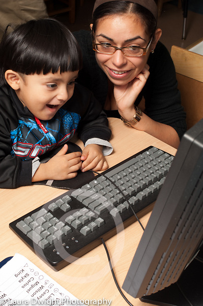 Preschool 3-4 year olds female teacher in training or therapist working with boy on computer vertical