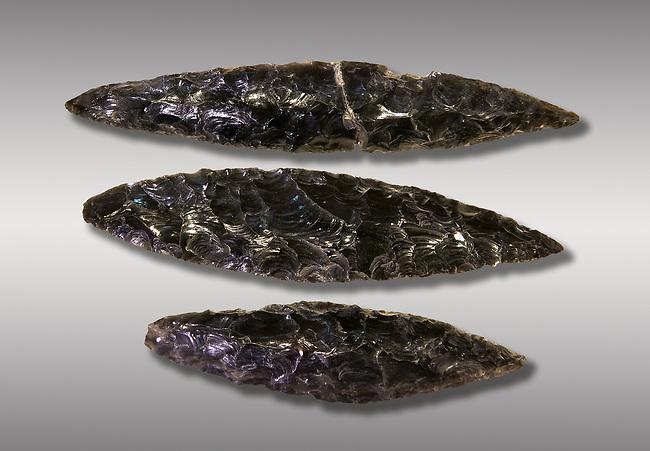 Black obsidian blades. Catalhoyuk Collections. Museum of Anatolian Civilisations, Ankara. Against a grey background