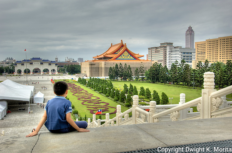 Young boy sits on the steps of the National Decomcracy Memorial Hall while gazing at the national Palace Museum in the distance