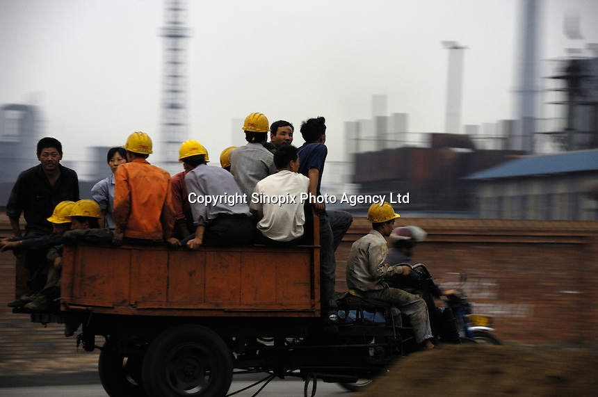 A tractor with a group of migrant workers on its trailer past a Coking & Gas factory in Xiaoyi, Shanxi, China..