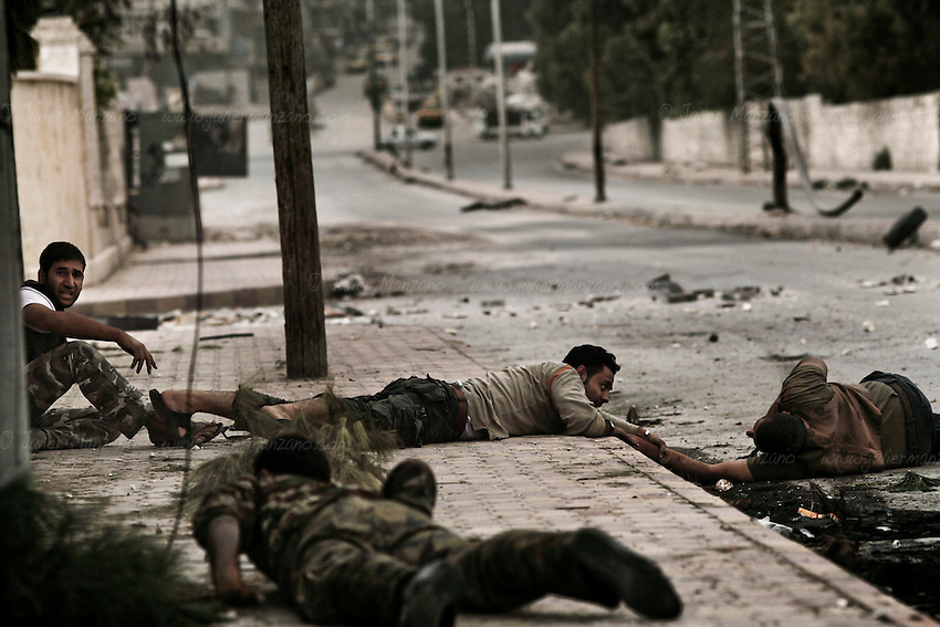 Free Syria Army soldiers crawled through the ground to reach him and pulled them towards a vehicle that rushed him to the hospital. It is not known if he survived. Three civilians were shot on this main road in the space of three hours by the same sniper. ..© Javier Manzano..012. Several vehicles drove past this man as he looked up in desperation (no one stopped because of the risk of being shot by the sniper). At a moment's notice, the man stood up and began to run towards the members of the Free Syria Army. As he approached the other side of the street, he was shot a second time, falling to the ground. Free Syria Army soldiers crawled through the ground to reach him and pulled them towards a vehicle that rushed him to the hospital. It is not known if he survived. Three civilians were shot on this main road in the space of three hours by the same sniper. ..© Javier Manzano.