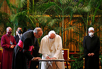 """Pope Francis signs a joint appeal during the meeting, """"Faith and Science: Towards COP26,"""" with religious leaders in the Apostolic Palace at the Vatican Oct. 4, 2021. The meeting was part of the run-up to the U.N. Climate Change Conference, called COP26, in Glasgow, Scotland, Oct. 31 to Nov. 12, 2021."""