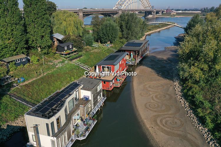 Foto: VidiPhoto<br /> <br /> NIJMEGEN – Vanaf de grond is het dinsdag nauwelijks te zien, maar vanuit de lucht tekenen de 'klimaatgolven' zich helder af tegen het strandje bij de woonschepen, aan de zijarm van de Waal bij Nijmegen. Volgens kunstenares Angela Vissers ligt door de klimaatverandering Nijmegen straks niet meer aan de Waal, maar aan zee. Vandaar dat ze met een stok -de opdracht was zo duurzaam mogelijk te schilderen- 'waarschuwende' golven tekende op het Waalstrandje. Het nadeel van de natuurtekening is wel dat een regenbui alles wegspoelt.