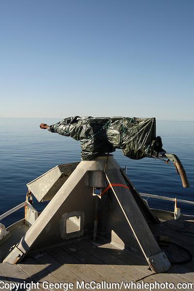Covered harpoon gun on bow of Norwegian whaling boat. Barents sea, Arctic Norway, North Atlantic.