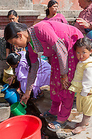 Nepal, Patan.  Woman Filling Plastic Pitcher at a Public Fountain.