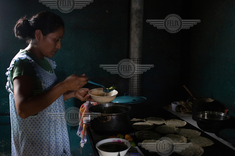 Ada Camposeco, 34, who was born in Chiapas, Mexico, while the community was there as war refugees, serves lunch for her family consisting of boiled potatoes and Chipilin leaves (Crotalaria longirostrata), known as chepil or longbeak rattlebox, along with corn tortillas at their home in the 15 de Octubre La Trinidad community. Ada's daughter Keren Esmeralda Esperanza was born while the community was living in a temporary shelter after the Fuego Volcano eruption in June 2018. Ada, a mother of three and married to Estuardo Lorenzo, states: ''For me, the word 'no' does not exist. This is what I tell my kids, to keep going regardless what comes your way!''