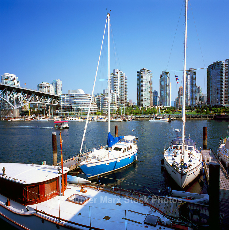 Vancouver, BC, British Columbia, Canada - Sailboats and Wooden Boat docked in False Creek at Granville Island, Granville Street Bridge and Yaletown Highrises in background