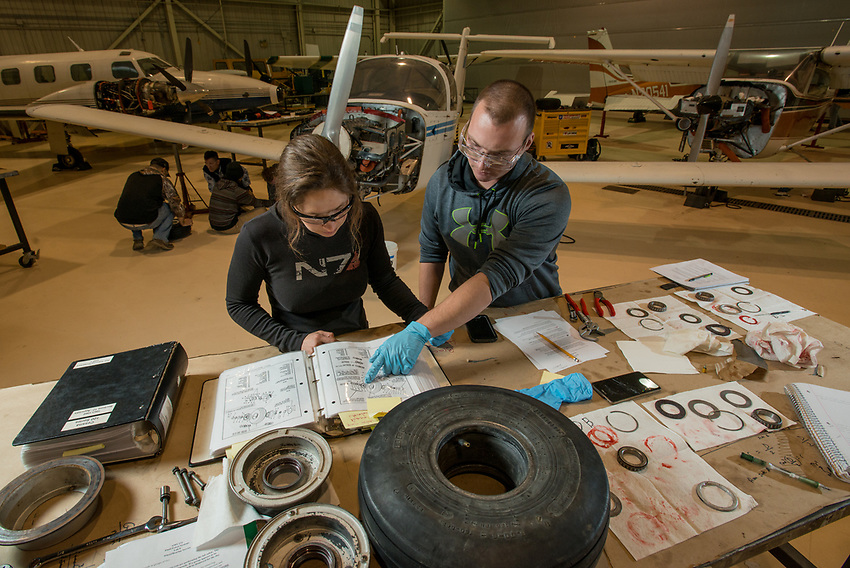 Aviation Maintenance Technology students Kaasan Braendel, left, and Matthew Schnell, right, disassemble and inspect aircraft landing gear during AMT 273 Aircraft Fluid Power Systems at UAA's Aviation Technology Complex on Merrill Field.