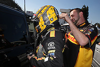 Feb. 14, 2013; Pomona, CA, USA; NHRA crew member for funny car driver Del Worsham helps secure his helmet during qualifying for the Winternationals at Auto Club Raceway at Pomona.. Mandatory Credit: Mark J. Rebilas-