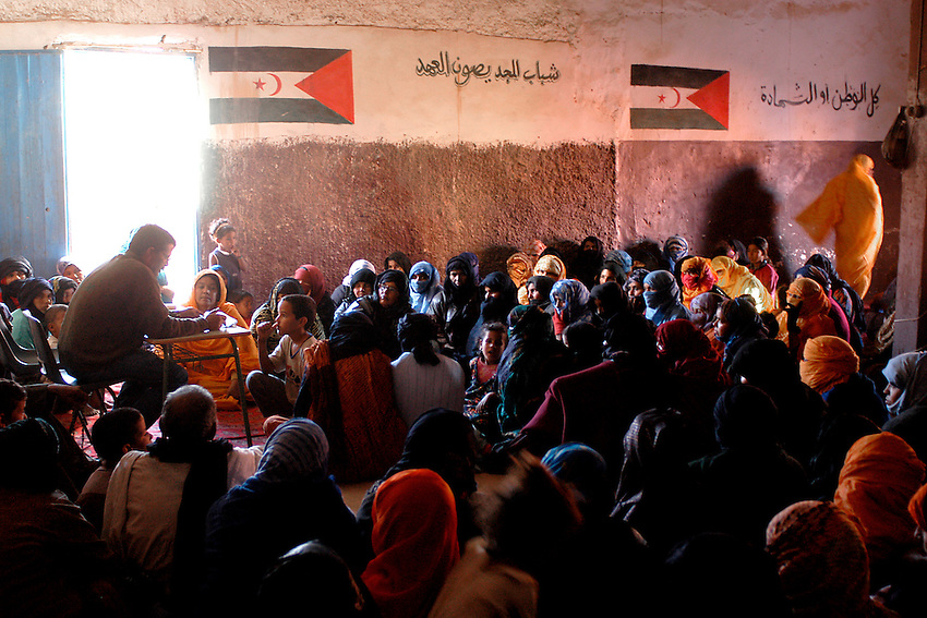 People attend a meeting on December 13, 2003 in the wilaya of Ausserd. Saharawi people have been living at the refugee camps of the Algerian desert named Hamada, or desert of the deserts, for more than 30 years now. Saharawi people have suffered the consecuences of European colonialism and the war against occupation by Moroccan forces. Polisario and Moroccan Army are in conflict since 1975 when Hassan II, Moroccan King in 1975, sent more than 250.000 civilians and soldiers to colonize the Western Sahara when Spain left the country. Since 1991 they are in a peace process without any outcome so far. (Ander Gillenea / Bostok Photo)