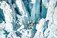 Helicopter flying amongst massive blocks of ice of Main Icefall on Franz Josef Glacier, Westland Tai Poutini National Park, West Coast, UNESCO World Heritage Area, New Zealand, NZ