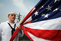 Information Systems Technician 2nd Class Ryan Allshouse prepares to raise the national ensign as the Nimitz-class aircraft carrier USS Ronald Reagan (CVN 76) pulls into Busan, South Korea, July 14, 2008, for a routine port visit. The Ronald Reagan Carrier Strike Group is on a deployment in the 7th Fleet area of responsibility. (U.S. Navy photo by Mass Communication Specialist 2nd Class Joe Painter/Released)