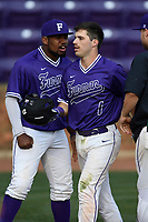 Second baseman Sims Griffith (1) of the Furman Paladins crosses the plate after scoring a run in game two of a doubleheader against the Harvard Crimson on Friday, March 16, 2018, at Latham Baseball Stadium on the Furman University campus in Greenville, South Carolina. Furman won, 7-6. (Tom Priddy/Four Seam Images)