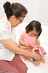 18 month old toddler girl with grandmother, who is holding toy so that child can insert sticks into holes