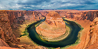 Panoramic view of iconic Horseshoe Bend's incised meander on the Colorado River under a cloudy, dramatic sky, near Page city in Arizona, USA