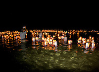 A man photographs the sight of hundreds of floating lanterns at the annual bon dance and Toro Nagashi (ìfloating lanterns set out to seaî) ceremony at Ali'i Beach Park in Haleiwa. Inscribed with the names of the departed, the lanterns ride the outgo