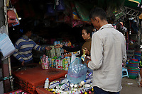 Battambang - Cambodia - June 2020<br /> -  early morning life around the river, buying small items in plastic bags.
