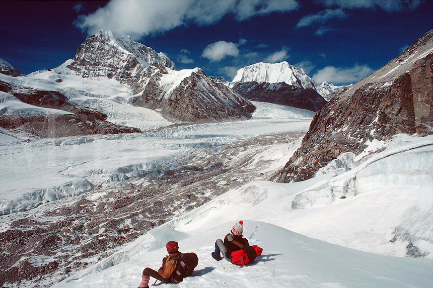 .Resting sherpas look out at peaks along the Drolambo Glacier, Rolwaling region, east Nepal...