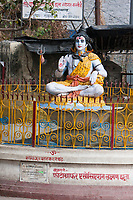 """India, Rishikesh.  Shiva Statue, with third eye, cobra necklace, and vibhuti markings (three horizontal lines) on forehead.  The sacred symbol """"om"""" is on his palm as he makes the vitarka mudra, the gesture oif discussion."""