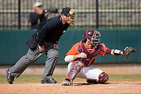 Catcher Steve Domecus #26 of the Virginia Tech Hokies sets a target for his pitcher as home plate umpire Danny Everett looks on at English Field March 27, 2010, in Blacksburg, Virginia.  Photo by Brian Westerholt / Four Seam Images
