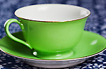 Green cup and saucer on blue table cloth.  Empty cup.  China cup.  Gold leaf.