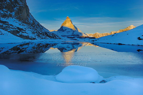 Matterhorn at sunrise in winter with reflection in the Riffelsee, Zermatt, Valais, Switzerland