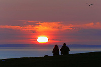 A couple make the most of the day as the sun sets in Rhossili