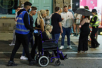 Pictured: A woman is taken away in a wheelchair in Wind Street, Swansea, Wales, UK. Saturday 07 August 2021<br /> Re: Nightclubs have reopened this weekend as most Covid restrictions have come to an end in Wales, UK.<br /> Pubs and restaurants were allowed to open for certain periods, with safety measures in place unlike nightclubs.