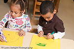 Education Preschool 3-5 year olds art activty boy and girl drawing with markers using opposite hands (either right or left hand)