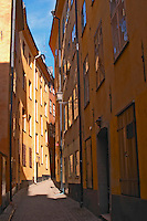 A graphic view of a narrow street in the Old Town Gamla Stan with a cobble stone street and ochre painted buildings. Stockholm, Sweden, Sverige, Europe