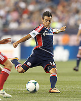 New England Revolution midfielder Diego Fagundez (14) takes a shot.  In a Major League Soccer (MLS) match, the New England Revolution (blue) defeated Chicago Fire (red), 2-0, at Gillette Stadium on August 17, 2013.