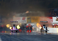 Oct 4, 2013; Mohnton, PA, USA; NHRA top fuel dragster driver Terry McMillen (left) races alongside Tony Schumacher during qualifying for the Auto Plus Nationals at Maple Grove Raceway. Mandatory Credit: Mark J. Rebilas-