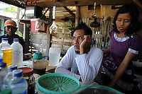 Owners of a warung (coffee shop), 42 year old Fathoni and his 36 year old wife Sulami, in Gempul Sari village, which sits on the edge of the mud flow zone. They lost their former jobs in a factory that was flooded, and live in fear of a breach of the mud dam. Since May 2006, more than 10,000 people in the Porong subdistrict of Sidoarjo have been displaced by hot mud flowing from a natural gas well that was being drilled by the oil company Lapindo Brantas. The torrent of mud - up to 125,000 cubic metres per day - continued to flow three years later.