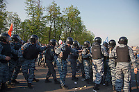 Moscow, Russia, 06/05/2012..Police take cover from objects thrown during opposition demonstration against Russian Presidential election results on the eve of Vladimir Putins inauguration as President.