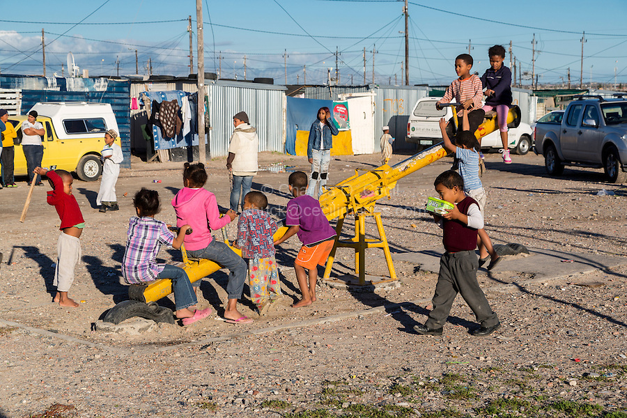 South Africa, Cape Town, Blikkiesdorp Township.  Children Playing in Playground, Houses in Background.