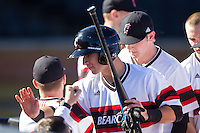 Devin Wenzel (8) of the Cincinnati Bearcats is congratulated by his teammates after scoring a run against the Radford Highlanders at Wake Forest Baseball Park on February 22, 2014 in Winston-Salem, North Carolina.  The Highlanders defeated the Bearcats 6-5.  (Brian Westerholt/Four Seam Images)