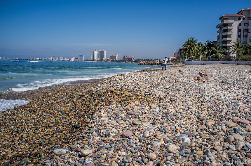 Fine Art Landscape Travel Photograph of a man fishing from a rocky beach in Puerto Vallarta, Mexico.