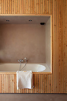 The ensuite bath in the master bedroom is built into a wood clad alcove