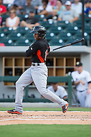 Julio Borbon (5) of the Norfolk Tides follows through on his swing against the Charlotte Knights at BB&T BallPark on July 17, 2015 in Charlotte, North Carolina.  The Knights defeated the Tides 5-4.  (Brian Westerholt/Four Seam Images)