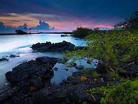 At sunset, Kiholo Bay's turquoise waters wrap around its rocky shoreline, Big Island.