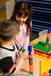 Education Preschool 3-4 year olds boy and girl playing with stacking pegs talking and interacting vertical