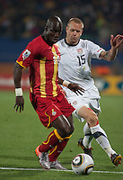 Ghana's Stephen Appiah dribbles the ball while being defended by the USA's Jay DeMerit in the second round of the 2010 FIFA World Cup match between USA and Ghana in Rustenberg, South Africa on Saturday, June 26, 2010.  Ghana won 2-1.