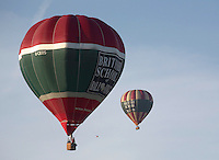The balloons rise up into the sky lifted by hot air from the propane burners, British School of ballooning, Ebernoe, West Sussex.