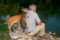The photographers husband- James Bumgarner MD- with enthusiastic friends - baby raccoon and fawn-- sharing his quiet moment at the lake