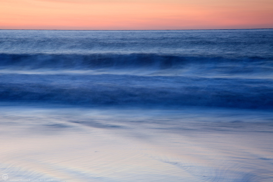 Waves roll softly ashore at sunset on a quiet beach in California
