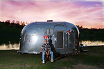 A man sitting in front of his Airstream Pacer with antlers on his head. The Airstream is decorated with Christmas lights and a Santa hat.