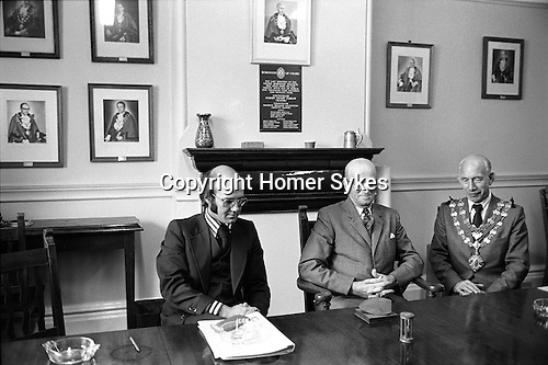 Letting of the Chard Market Tolls. The Guildhall, Chard Somerset. April 1975;<br /> Mayor of Chard, Maurice Lillington, right, past Mayor Ernest Ashman (Mayor 1950-52), centre, and on the left George Smith, an official with the then Yeovil District Council. George Smith was really dynamic, became economic development officer and was a huge benefit to South Somerset. He was only 50 when he died, and a road on one of the business parks was named George Smith Way in his memory. (Thanks Tina Rowe)<br /> A Royal Charter dating back to 29th June 1683 empowered the town to hold three annual fairs and three weekly markets on Tuesdays, Thursdays and Saturdays.  <br /> Historically the right to let the tolls has lain with the burgesses and then Chard Borough Council, but on reorganisation in 1974 the responsibility moved to the new District Council. Chard market tolls are auctioned off against the clock, as sand trickled through an hourglass. After the sand has run out once, the hourglass is turned and further bids could still be made. The sand had to run out a total of three times before the final lessee was decided.<br /> In 1975, the market was held on Boden Street car park, and there were only two or three stalls. ( Four people attended the auction ) Later the site moved to an old Lace Mill, and then they were held in the street. The hourglass auctions ended in the later 1980s because the tolls were becoming more valuable and there were even threats of violence as traders vied with each other.